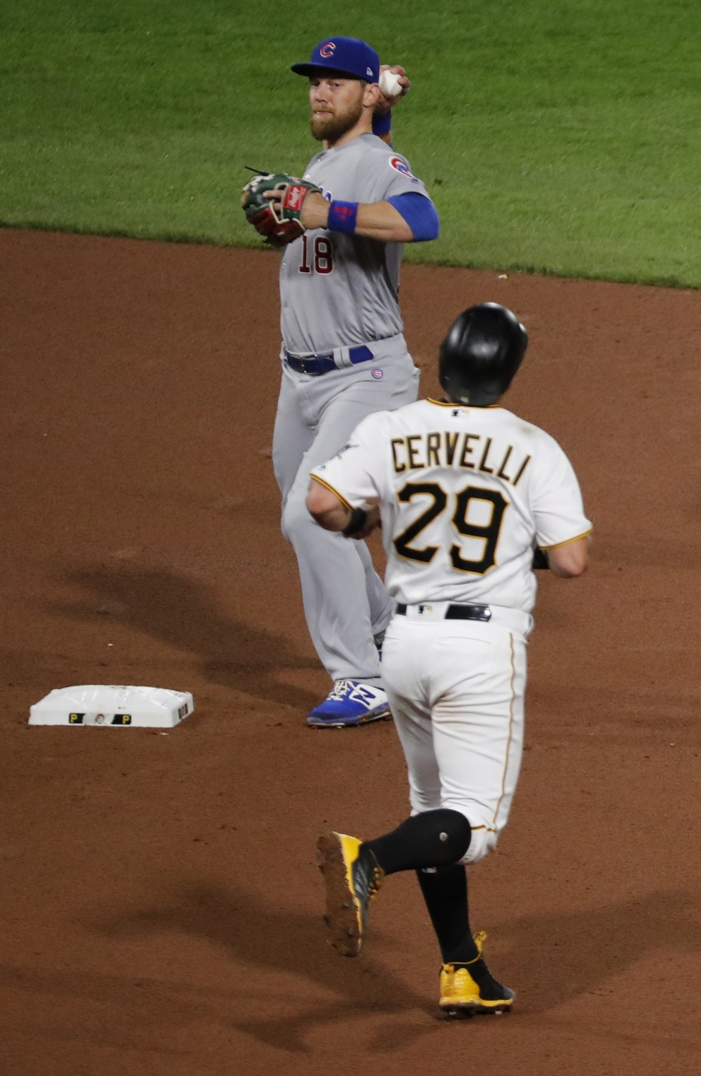 Pittsburgh Pirates' Francisco Cervelli (29) heads toward second as Chicago Cubs second baseman Ben Zobrist, top, relays the ball on to first to comple...