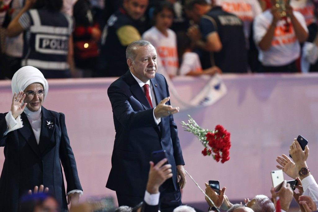 Turkey's President Recep Tayyip Erdogan, accompanied by his wife Emine, left, throws flowers to his supporters as he arrives to deliver a speech at hi...