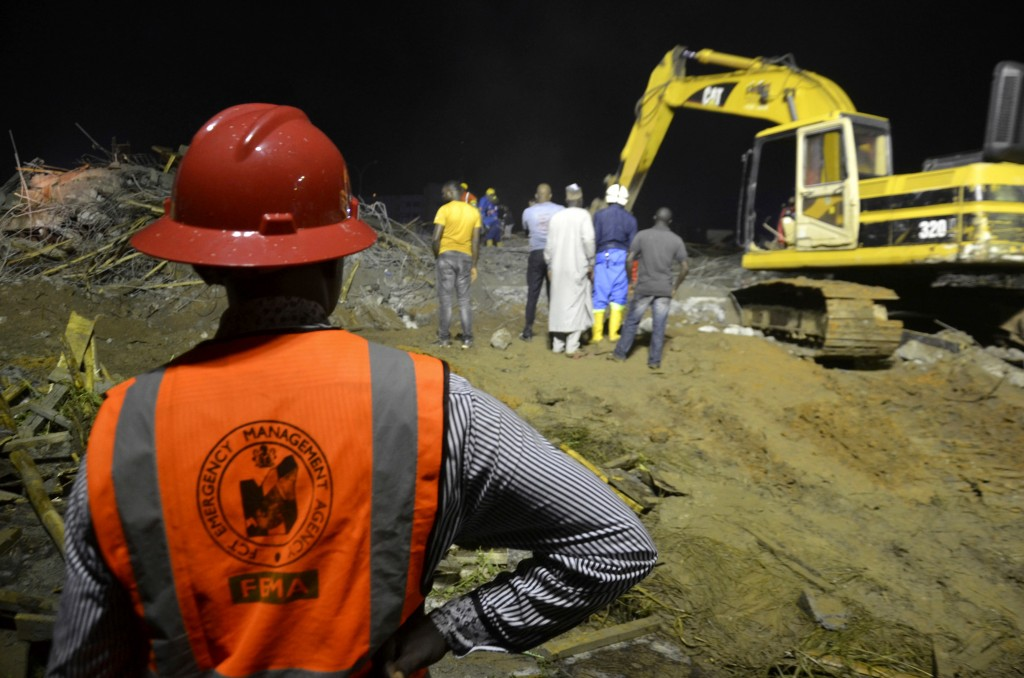 Rescue workers search for trapped people under the rubble of a collapsed shopping complex that was under construction in Abuja, Nigeria, Friday, Aug 1...