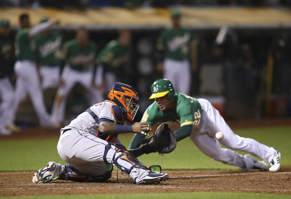 Oakland Athletics' Ramon Laureano, right, starts his slide as Houston Astros catcher Martin Maldonado waits for the ball in the ninth inning of a base...