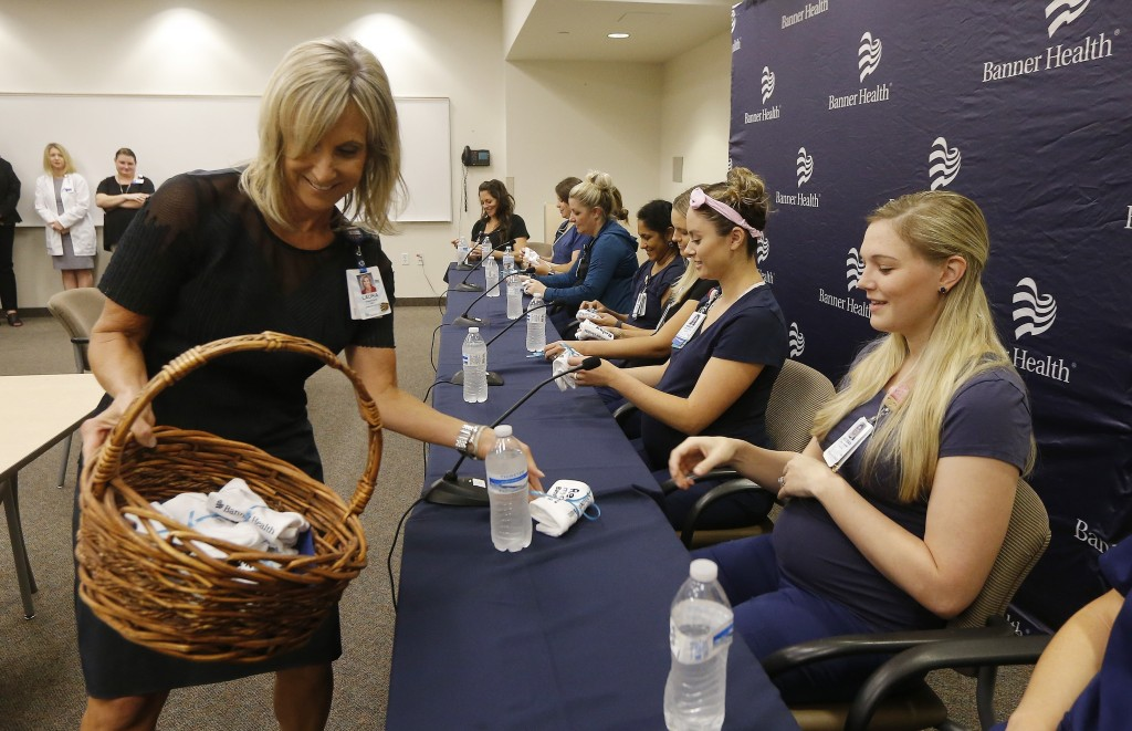 Banner Desert Medical Center CEO Laura Robertson, left, hands out baby outfits Friday, Aug. 17, 2018, in Mesa, Ariz., to the sixteen pregnant nurses w...