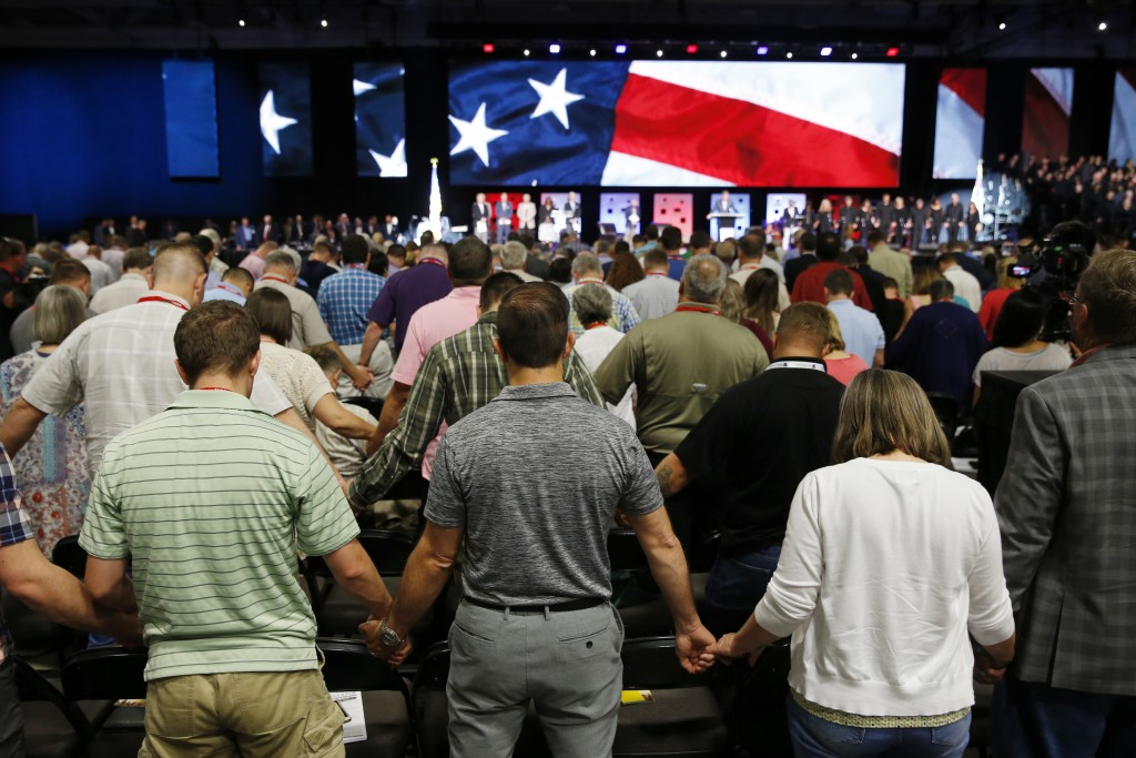 FILE - In this Tuesday, June 12, 2018 file photo, people pray for America at the 2018 Annual Meeting of the Southern Baptist Convention at the Kay Bai...