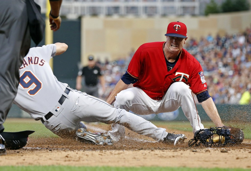 Minnesota Twins pitcher Kyle Gibson, right, covers the plate but Detroit Tigers' Nicholas Castellanos (9) beats the tag to score on a wild pitch by Gi...