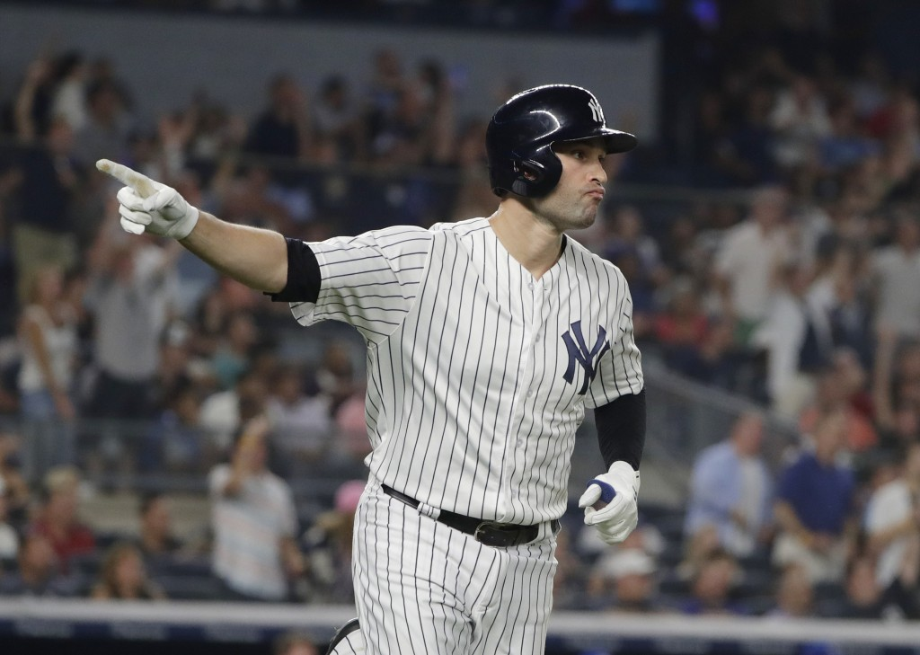 New York Yankees' Neil Walker points as he runs up the first base line after hitting a three-run home run during the fourth inning of a baseball game ...