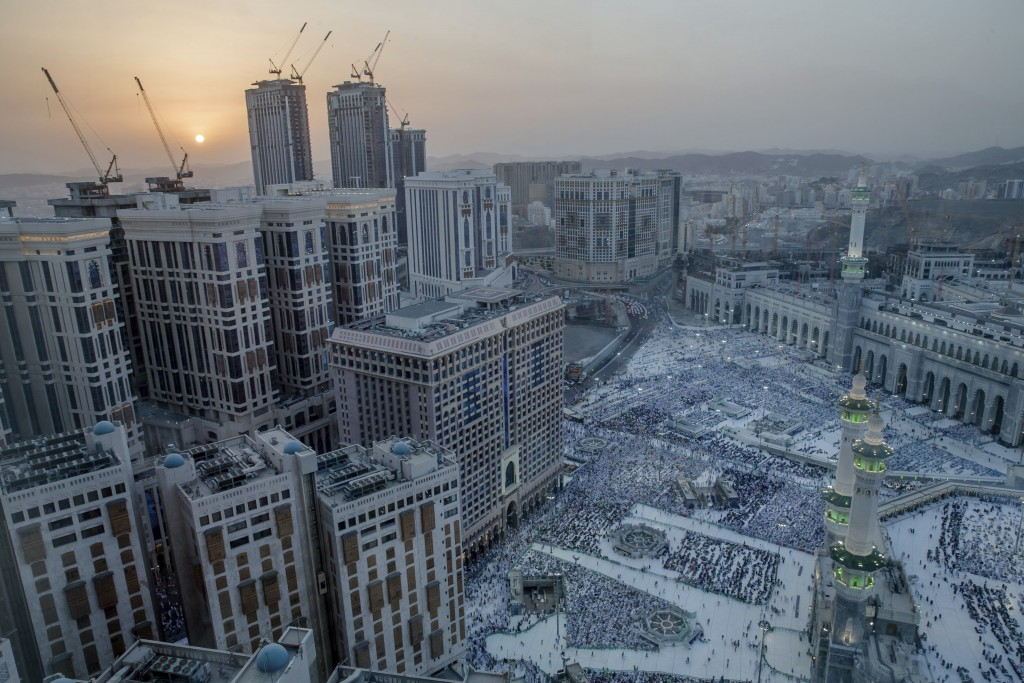 The sun sets over the city of Mecca as Muslim pilgrims wait to offer evening prayers inside the Grand Mosque, ahead of the annual Hajj pilgrimage, in ...