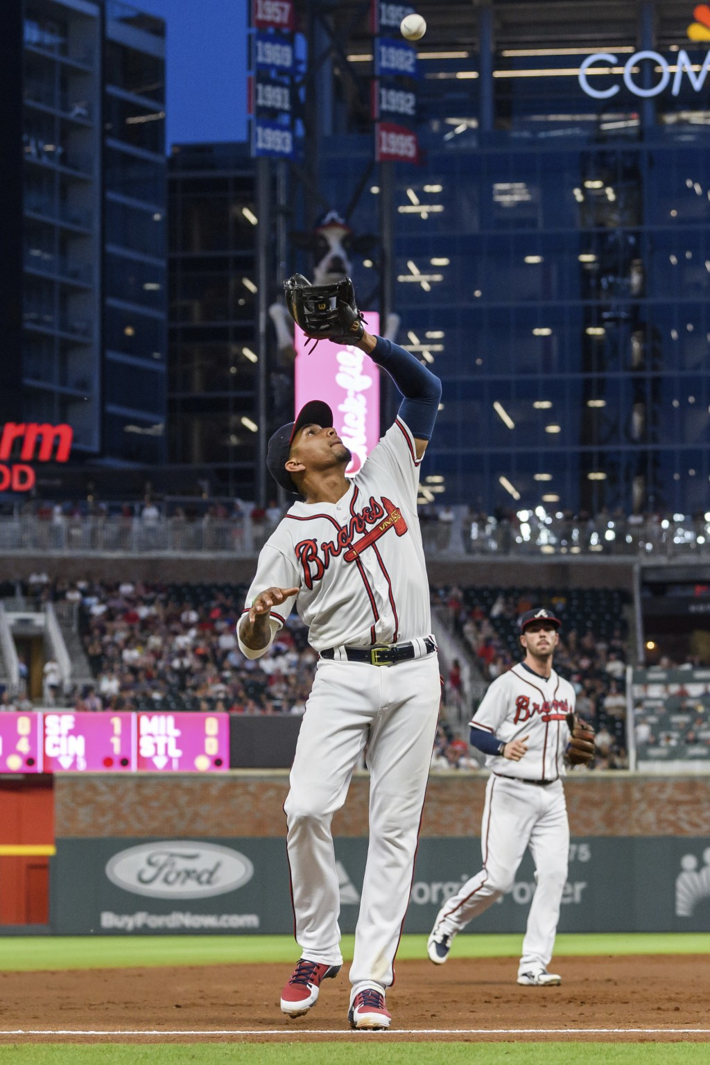 Atlanta Braves third baseman Johan Camargo catches the ball for an out on Colorado Rockies' Carlos Gonzalez during the third inning of a baseball game...
