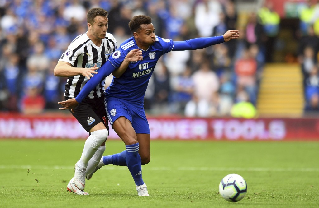 Newcastle United's Javier Manquillo, left, presses Cardiff City's Josh Murphy during their English Premier League soccer match at the Cardiff City Sta...