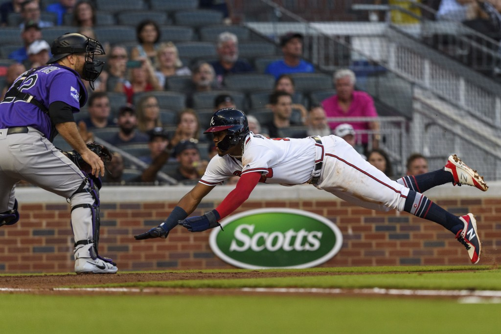 Atlanta Braves' Ronald Acuna Jr. dives toward home plate to score on a sacrifice fly ball as Colorado Rockies catcher Chris Iannetta (22) waits for th...