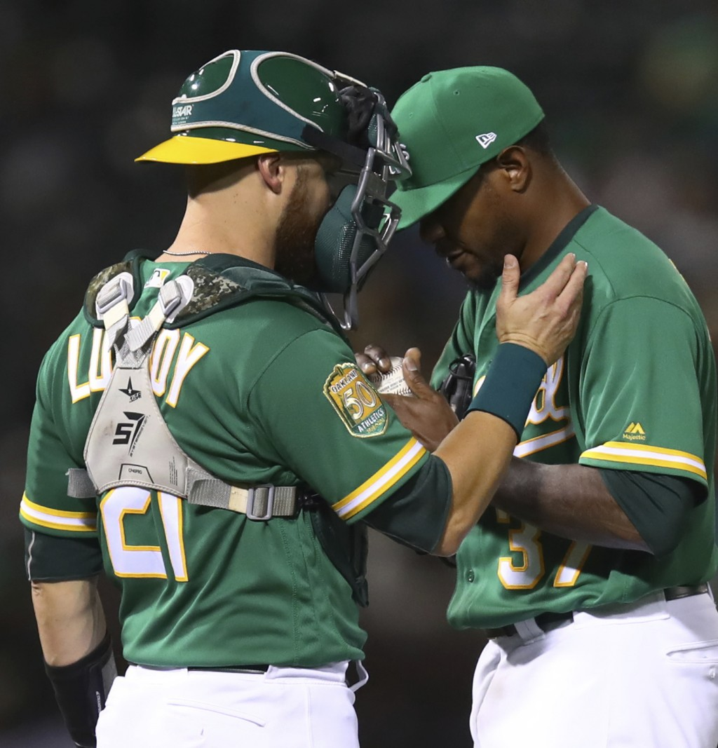 Oakland Athletics' Edwin Jackson, right, meets with Jonathan Lucroy during the fifth inning of the team's baseball game against the Houston Astros on ...