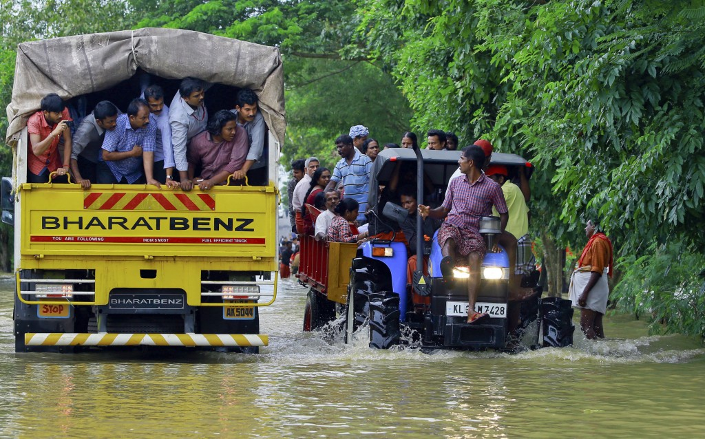 Flood affected people are rescued in a tractor, right as volunteers go for rescue work in a truck, left, at Kainakary in Alappuzha district, Kerala st...