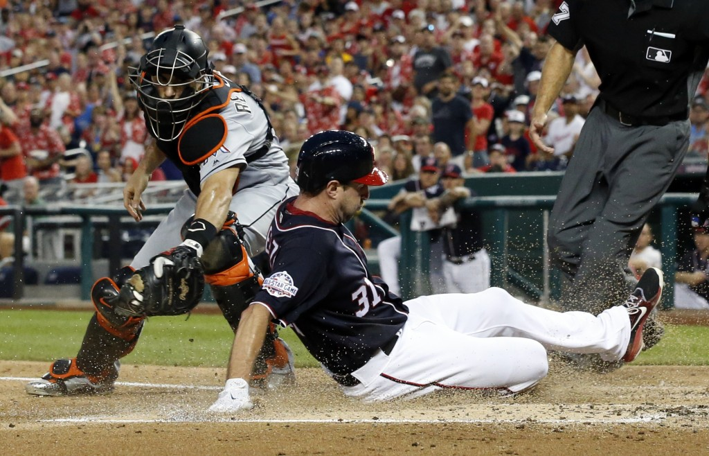 Miami Marlins catcher J.T. Realmuto can't make the tag on Washington Nationals' Max Scherzer, who is safe at home on the single by Bryce Harper during...