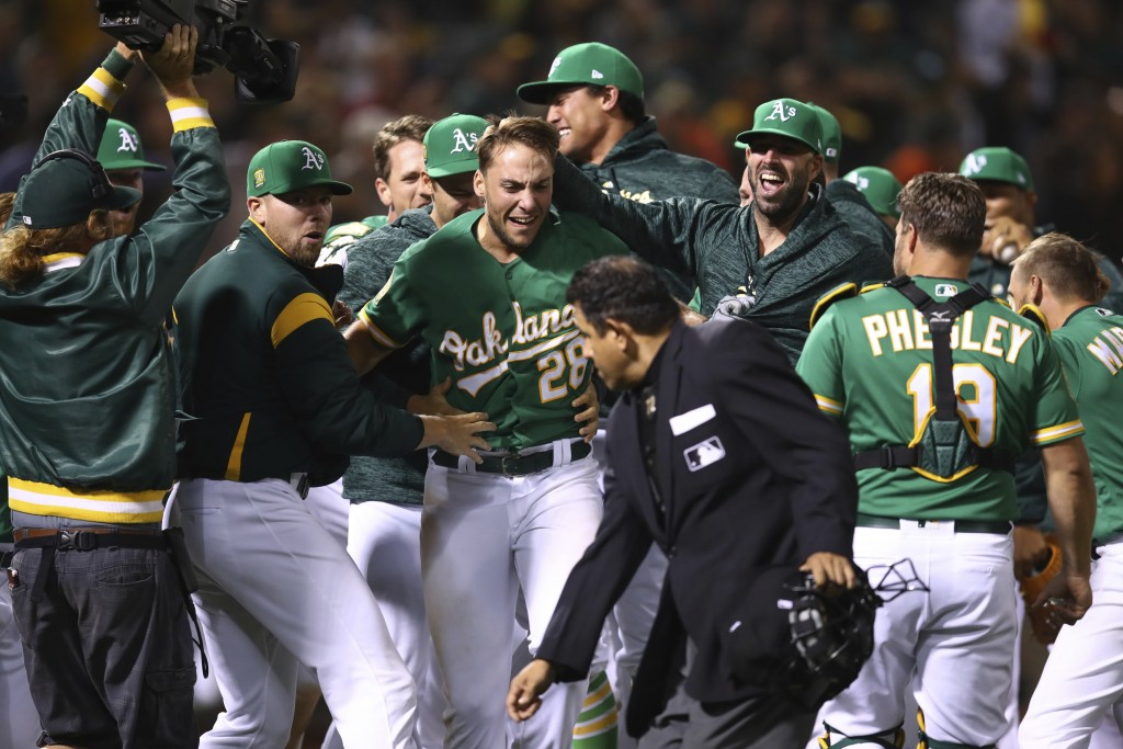 Oakland Athletics' Matt Olson (28) celebrates after hitting the game winning home run off Houston Astros' Tony Sipp in the tenth inning of a baseball ...