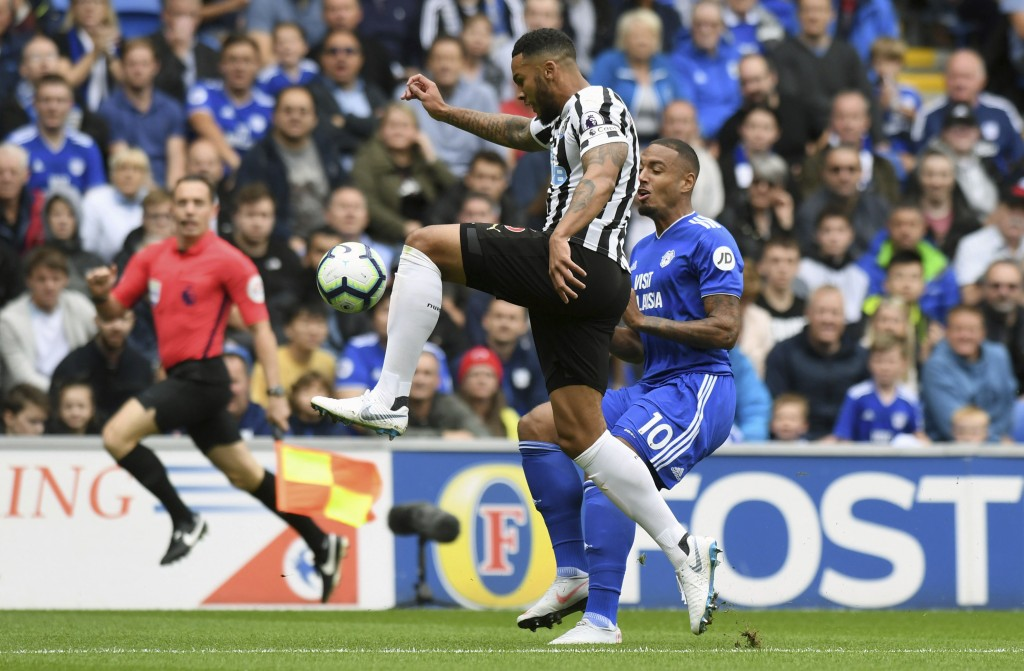 Newcastle United's Jamaal Lascelles, centre left, and Cardiff City's Kenneth Zohore during their English Premier League soccer match at the Cardiff Ci...