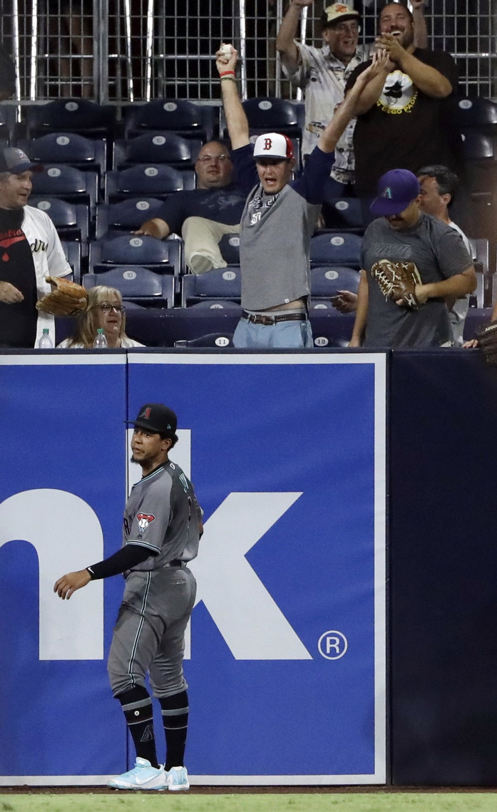 A fan reacts after catching a home run ball hit by the San Diego Padres' Manuel Margot as Arizona Diamondbacks center fielder Jon Jay, below, looks on...