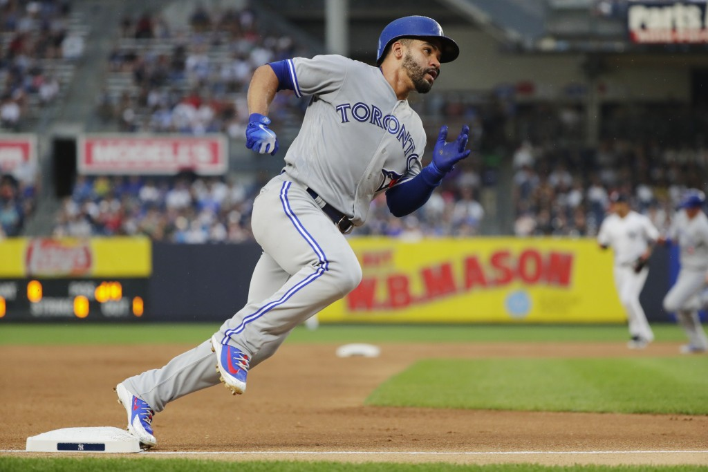 Toronto Blue Jays' Devon Travis runs to home plate on a single by Kendrys Morales during the first inning of a baseball game against the New York Yank...