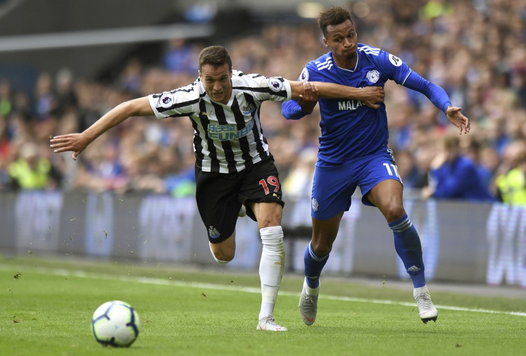 Newcastle United's Javier Manquillo, left, and Cardiff City's Josh Murphy chase the ball during their English Premier League soccer match at the Cardi...