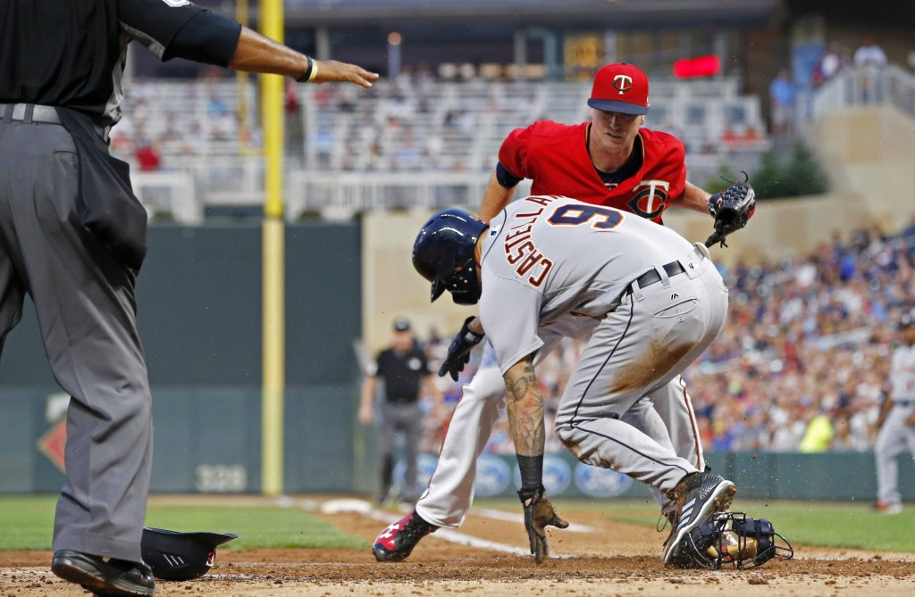 Minnesota Twins pitcher Kyle Gibson, top, covers the plate but Detroit Tigers' Nicholas Castellanos (9) beats the tag to score on a wild pitch by Gibs...