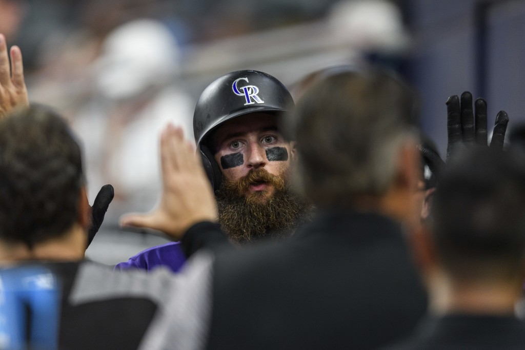 Colorado Rockies' Charlie Blackmon high-fives teammates after scoring on a wild pitch by Atlanta Braves reliever Chad Sobotka during the sixth inning ...