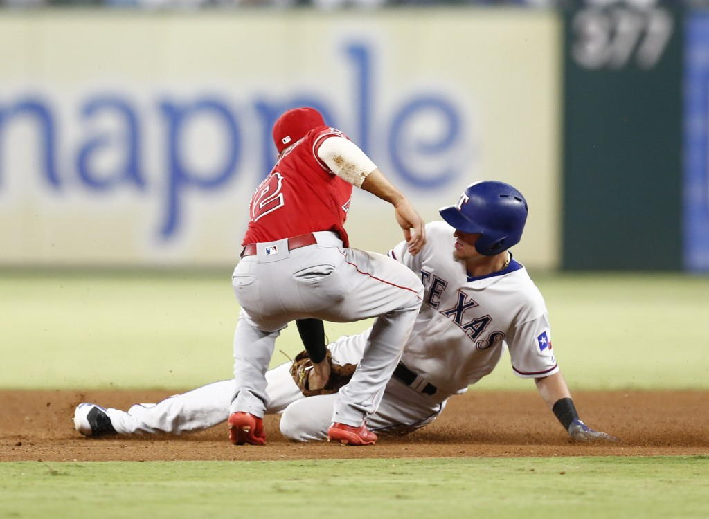 Los Angeles Angels shortstop Andrelton Simmons (2) tags out Texas Rangers' Carlos Tocci, right, on a ground-out by Shin-Soo Choo during the fourth inn...