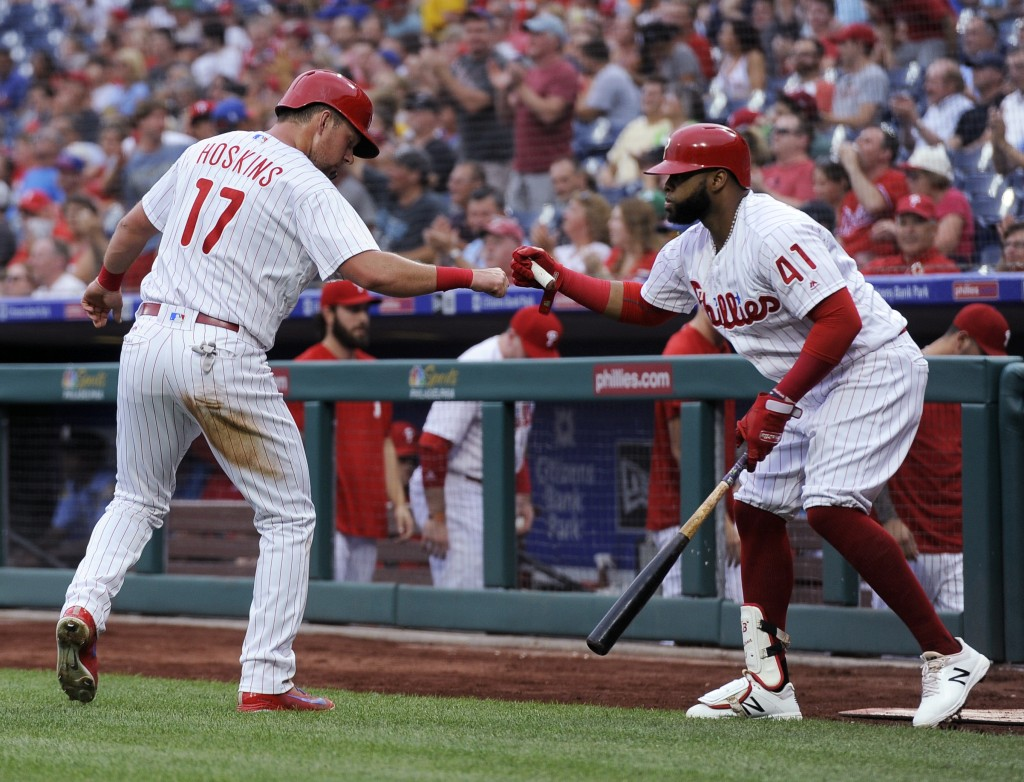 Philadelphia Phillies' Rhys Hoskins (17) celebrates with Carlos Santana (41) after scoring a run on a Nick Williams single during the first inning of ...