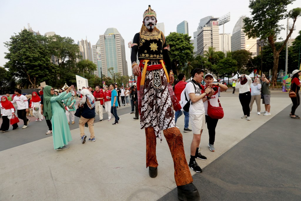 An Indonesia man walk on stilts prior the opening ceremony for the 18th Asian Games in Jakarta, Indonesia, Saturday, Aug. 18, 2018. (AP Photo/Tatan Sy...