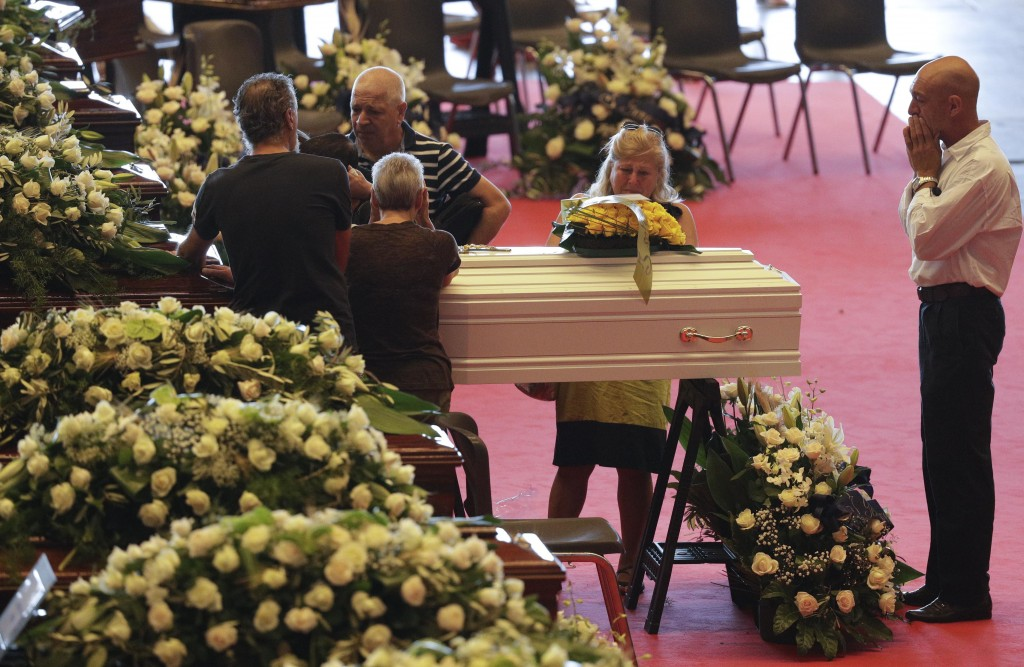 People stand by a small white coffin of a victim of a collapsed highway bridge prior to the start of the funeral service, in Genoa, Italy, Saturday, A...