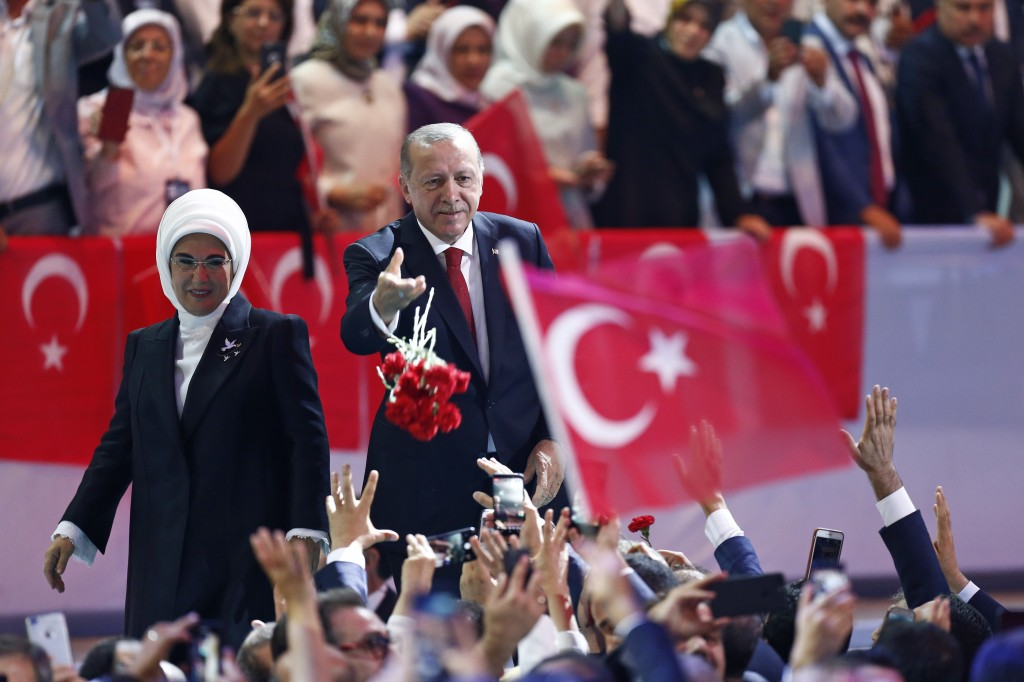 Turkey's President Recep Tayyip Erdogan, center, accompanied by his wife Emine, left, throws flowers to his supporters as he arrives to deliver a spee...