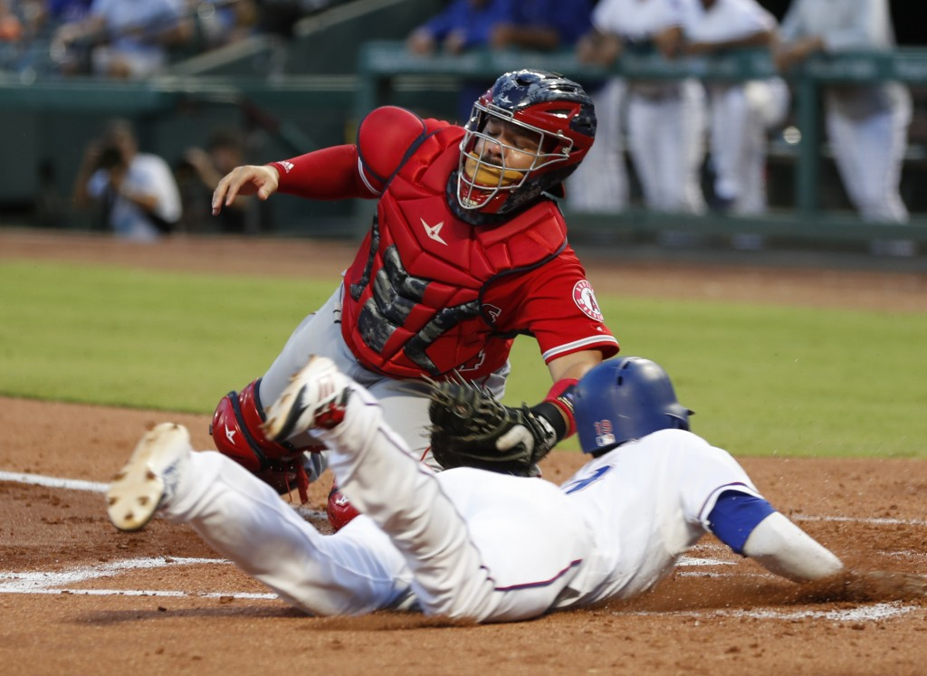 Texas Rangers' Jurickson Profar, foreground, slides and scores ahead of the tag by Los Angeles Angels catcher Rene Rivera on a double by Joey Gallo du...