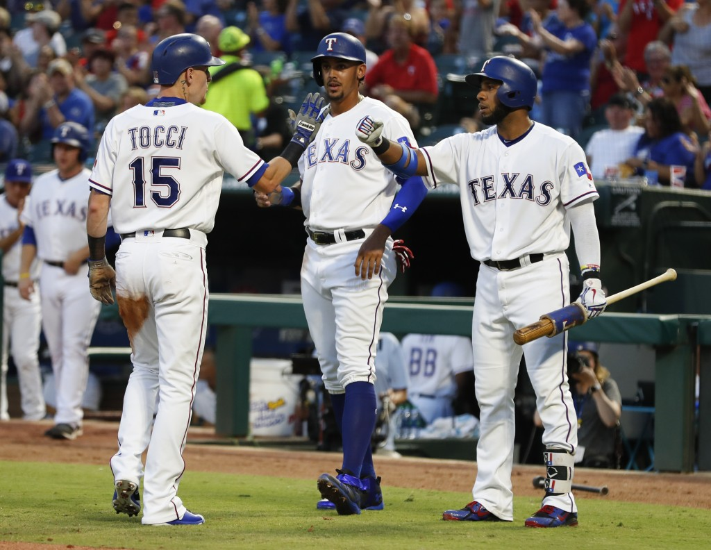 Texas Rangers' Elvis Andrus, right, celebrates with Carlos Tocci (15) and Ronald Guzman, center, after Tocci and Guzman scored on a single by Rougned ...