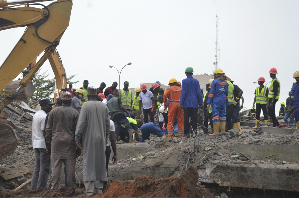Rescue workers search for people who may be trapped under the rubble of a collapsed under construction building in Abuja Nigeria, Friday, Aug. 17, 201...
