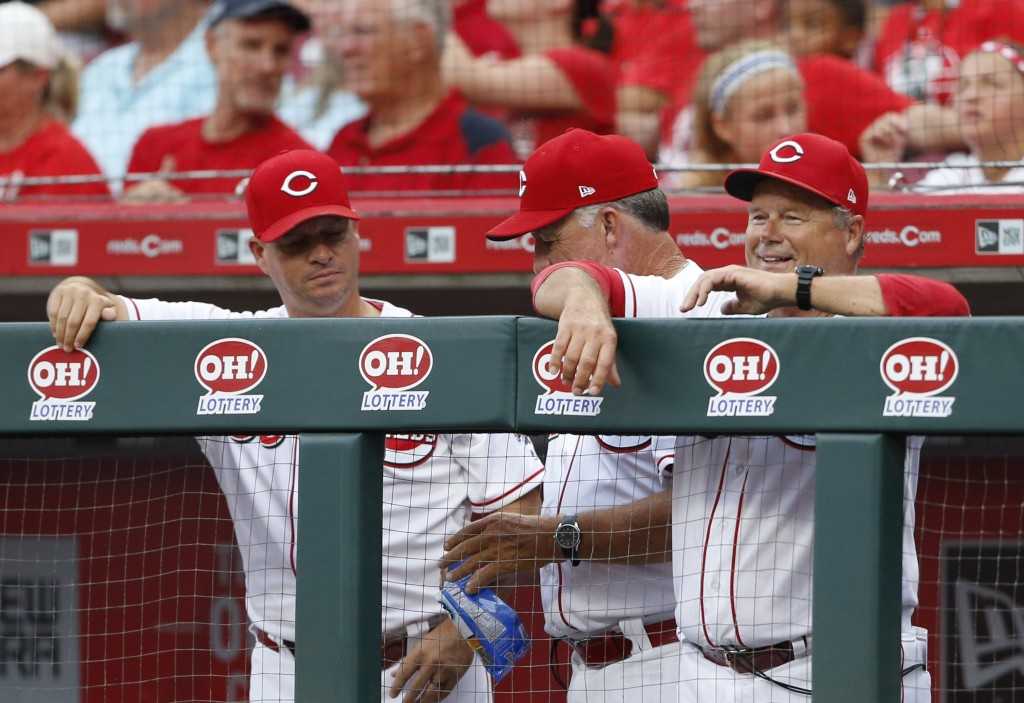Cincinnati Reds interim bench coach Pat Kelly, right, smiles as he watches his son San Francisco Giants starting pitcher Casey Kelly take the mound ag...