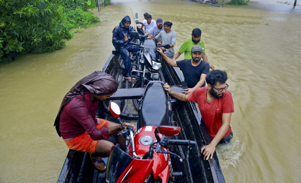 People salvage motorcycles in a country boat in a flooded area at Kainakary in Alappuzha district, Kerala state, India, Friday, Aug. 17, 2018. Rescuer...