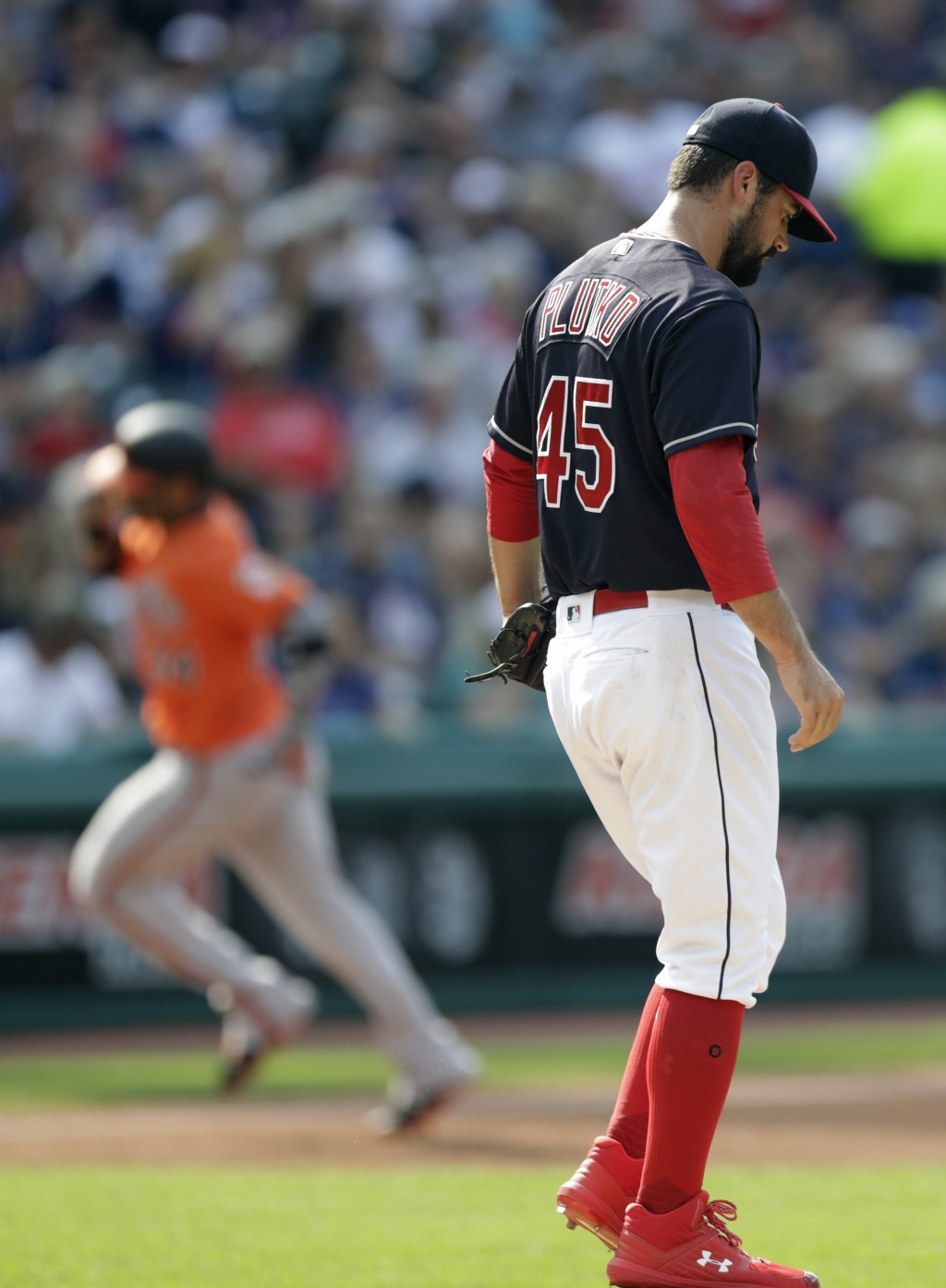 Cleveland Indians starting pitcher Adam Plutko, right, waits for Baltimore Orioles' Jonathan Villar to run the bases after Villar hit a three-run home...