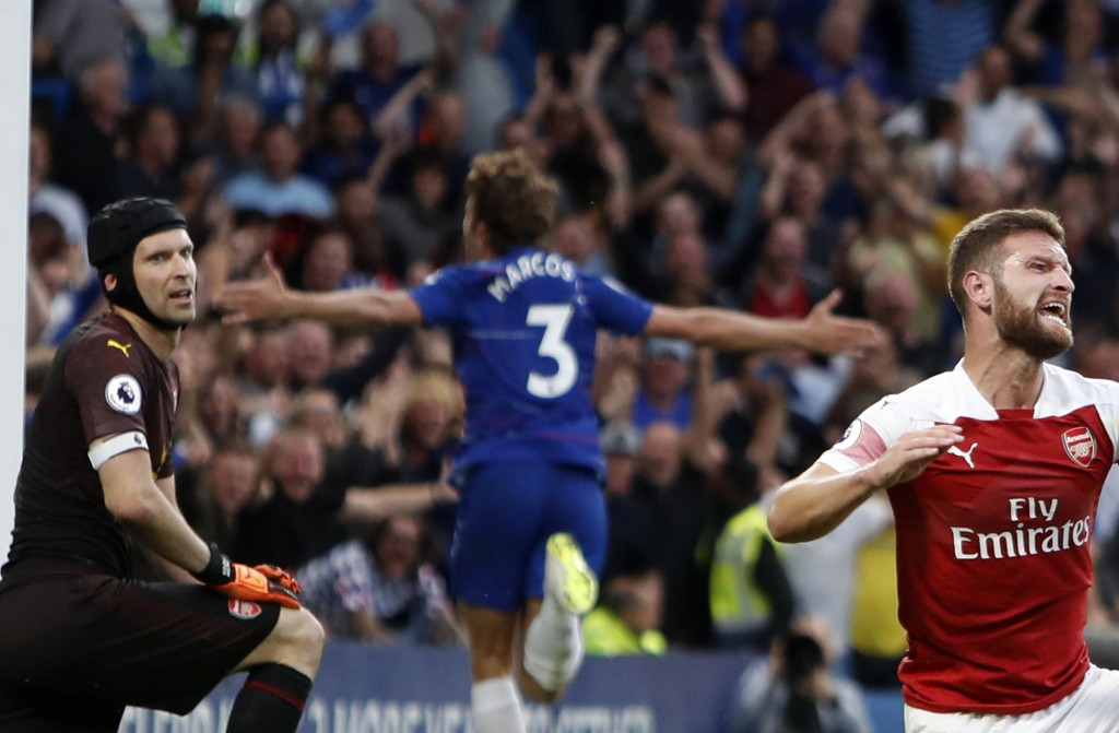 Arsenal's goalkeeper Petr Cech, left, and Arsenal's Shkodran Mustafi, right, react after Chelsea's Marcos Alonso, center, scores his side's third goal...
