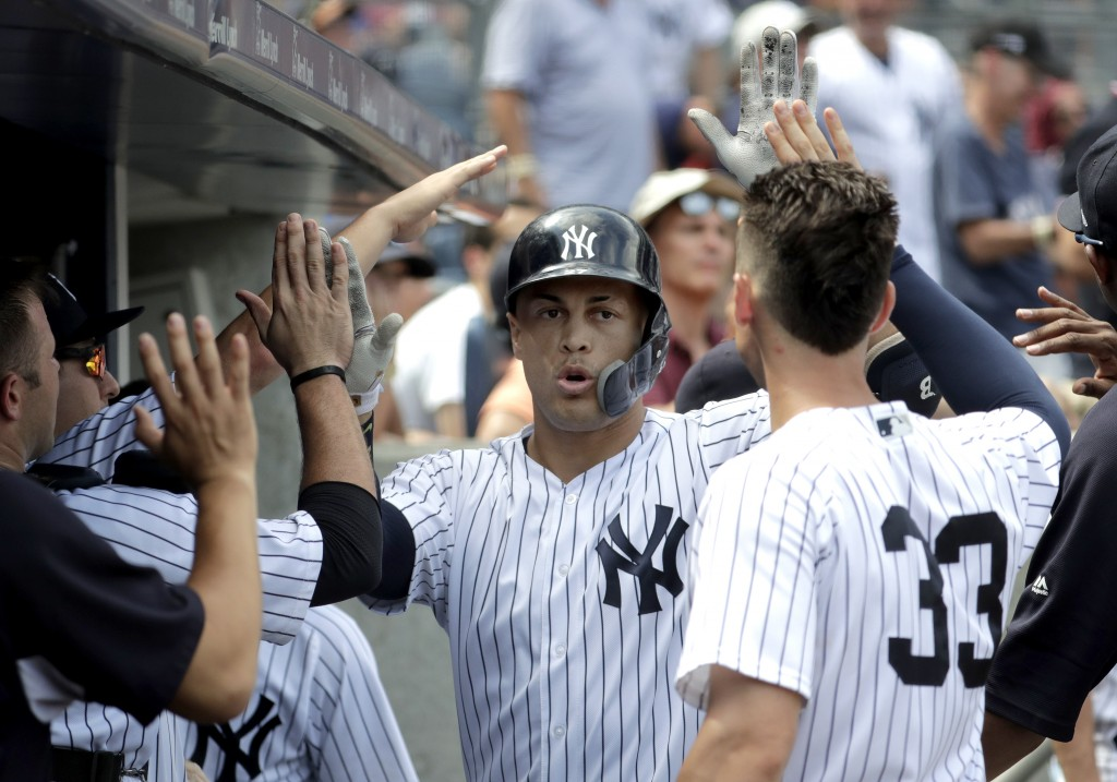 New York Yankees' Giancarlo Stanton, center, is congratulated after hitting a solo home run off Toronto Blue Jays starting pitcher Sean Reid-Foley dur...