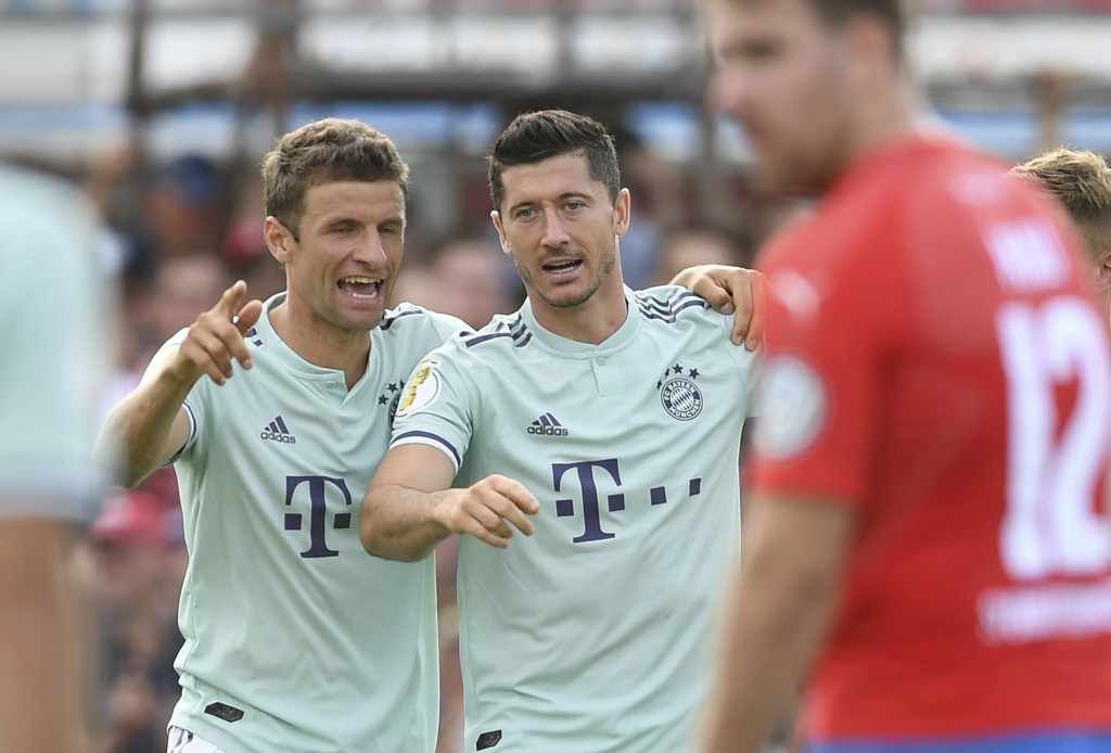 Bayern's Robert Lewandowski celebrates with his teammate Thomas Mueller, left, after scoring the opening goal during the German Soccer Cup, DFB-Pokal,...