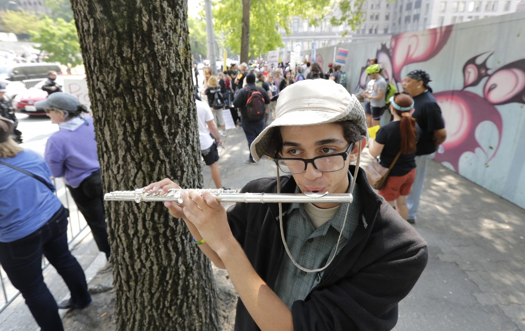 Mikaele Baker plays the flute as he stands on the side of the street of anti-fascist groups counter-protesting as members of Patriot Prayer and other ...