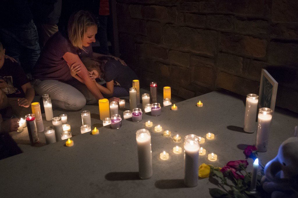 Jeanna Dietz hugs her daughter Eva, 7, while looking onto memorial on the front porch while others gather for a candle-lit vigil for Shanann Watts and...