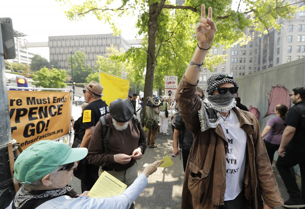 A protester holds up a peace sign while marching on the side of the street of anti-fascist groups counter-protesting as members of Patriot Prayer and ...