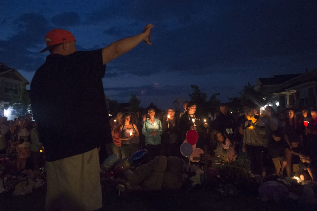 A neighbor holds a phone up to the crowd while live-streaming during a candle-lit vigil for Shanann Watts and her two daughters, Bella, 4, and Celeste...