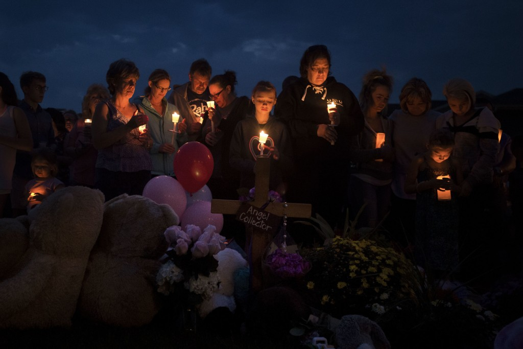 Mourners gather in front of a memorial for a candle-lit vigil for Shanann Watts and her two daughters, Bella, 4, and Celeste, 3, in front of the Watts...