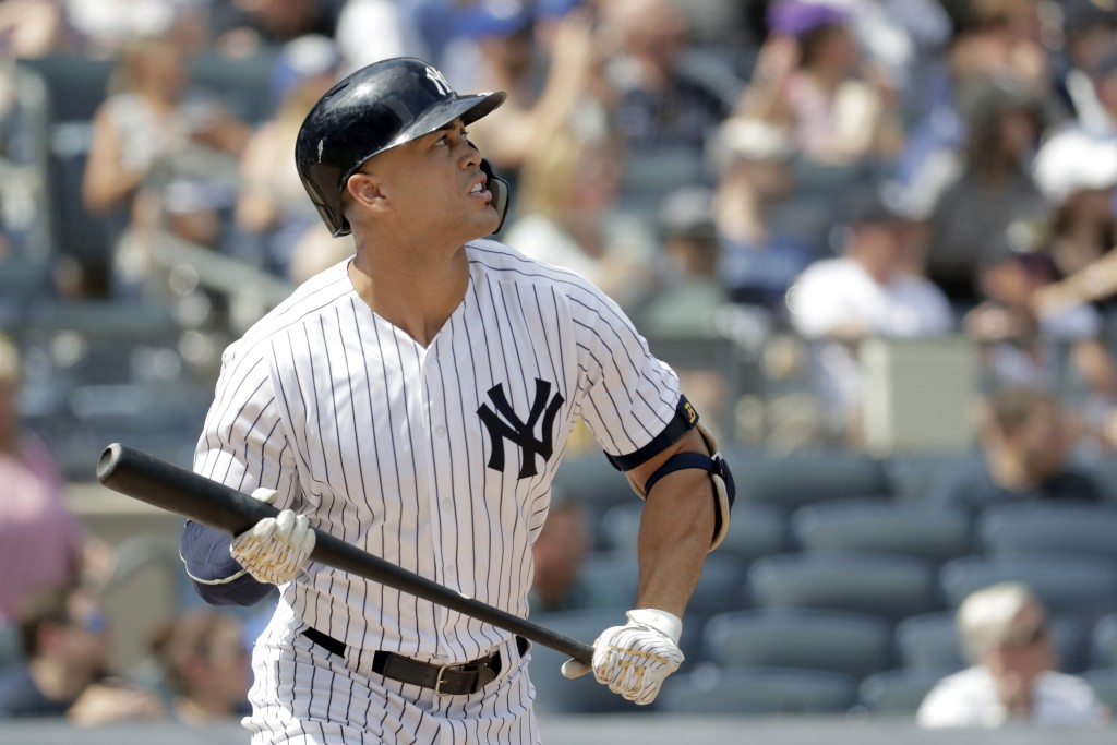 New York Yankees' Giancarlo Stanton watches his solo home run off Toronto Blue Jays starting pitcher Sean Reid-Foley during the fourth inning of a bas...