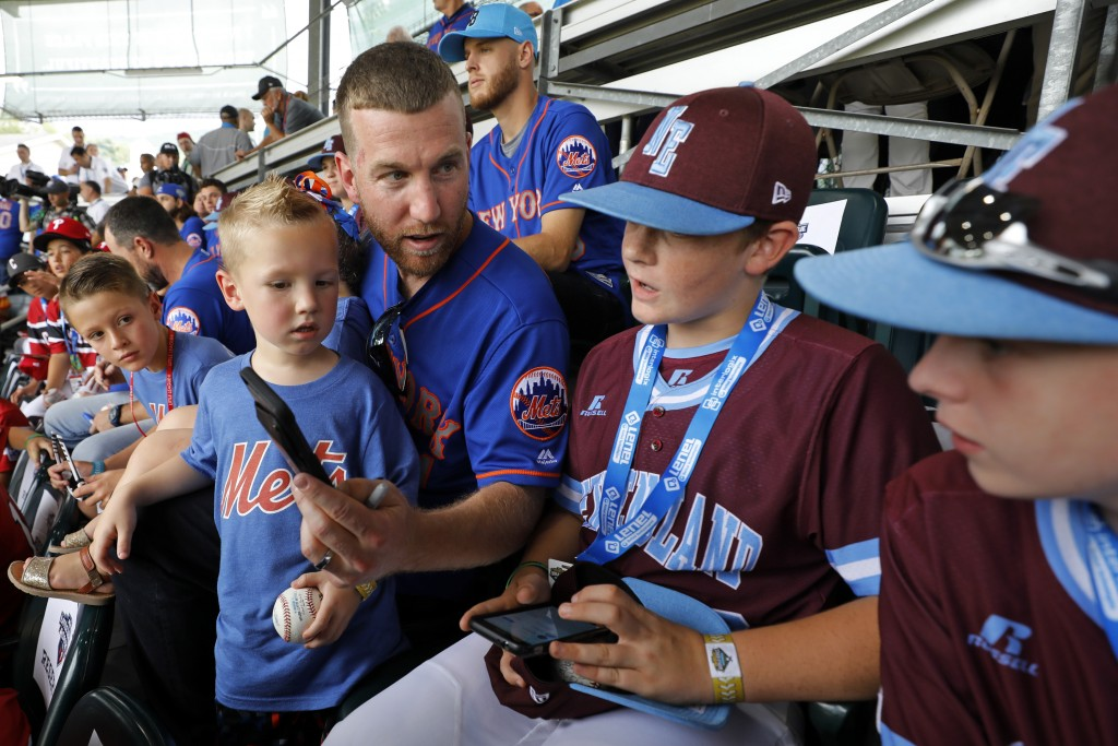 New York Mets' Todd Frazier, second from left, holds his son Blake as he asks Coventry, Rhode Island players Paulie Manfredo, second from right, and A...