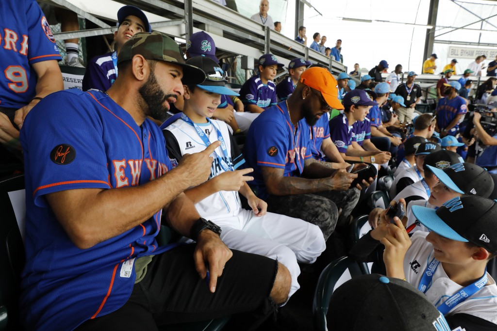 New York Mets' Jose Bautista, left, has a picture taken with Coeur d'Alene, Idaho's Alexander Currie (14) while taking in a baseball game in Internati...