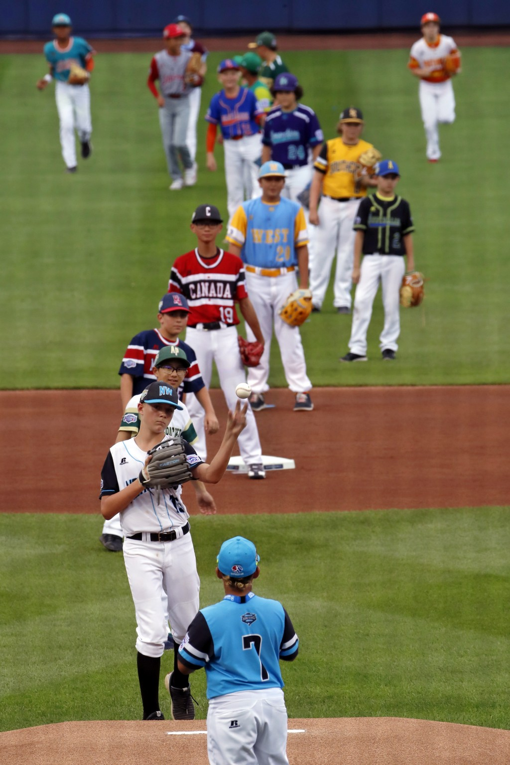 Coeur d'Alene, Idaho's Austin DeBoer, second from bottom, tosses ball to Panama's Carlos Arcia (7) to complete the ceremonial first pitch involving a ...