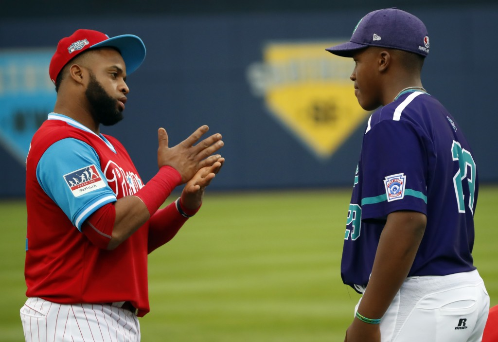Philadelphia Phillies first baseman Carlos Santana, left, talks with Spain's Ronald Vizcaino (29) on the field before the game against the New York Me...
