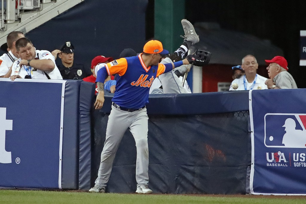 New York Met first baseman Wilmer Flores tries to help second baseman Jeff McNeil who went over the wall in a failed pursuit of a foul ball hit by Phi...