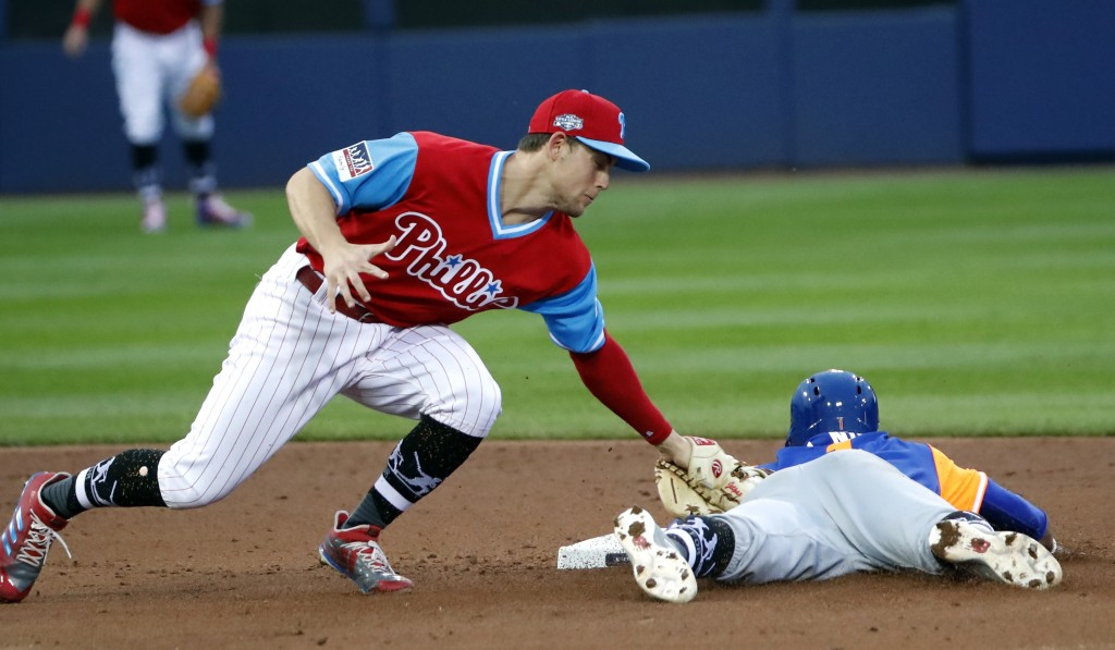 Philadelphia Phillies shortstop Scott Kingery, left, tags out New York Mets' Amed Rosario who was attempting to steal second base in the second inning...