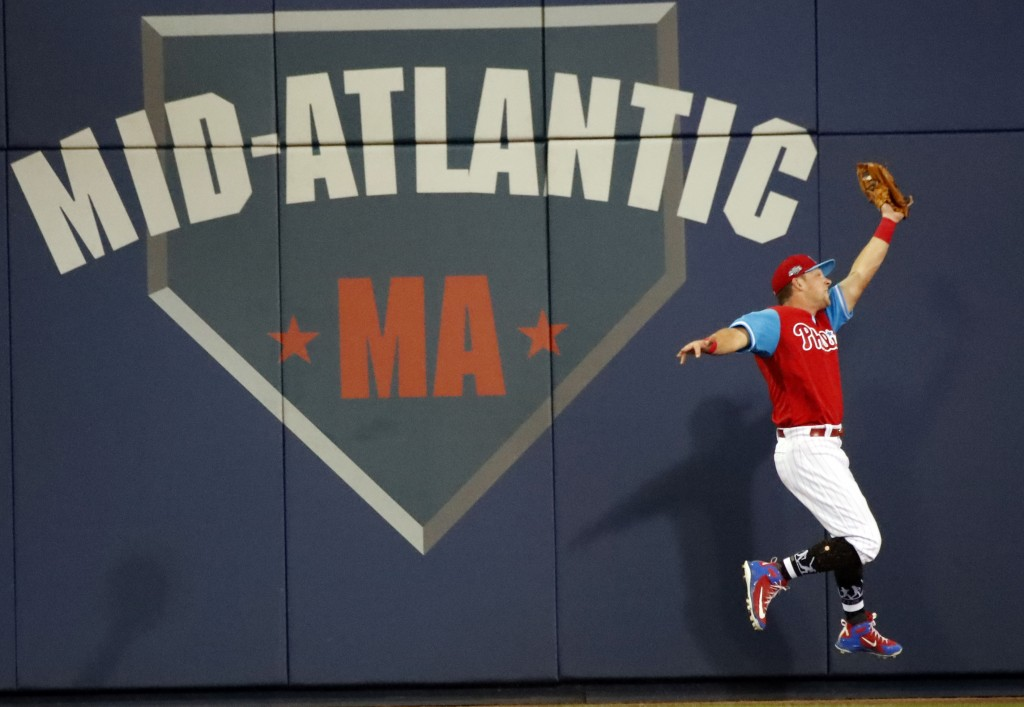 Philadelphia Phillies left fielder Rhys Hoskins makes a catch at the wall on a ball hit by New York Mets' Kevin Plawecki in the fourth inning of the L...