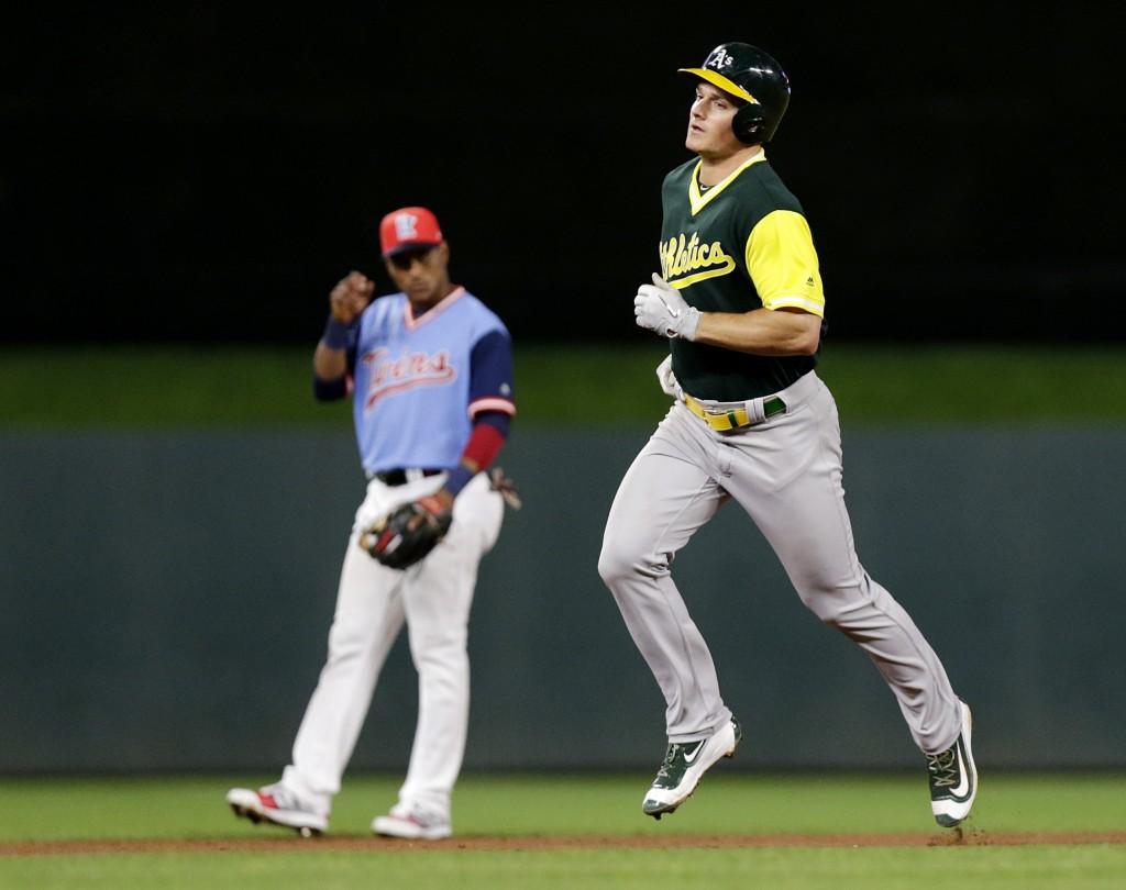 Oakland Athletics' Matt Chapman, right, rounds the bases past Minnesota Twins' Jorge Polanco after hitting a three-run home run against the Minnesota ...